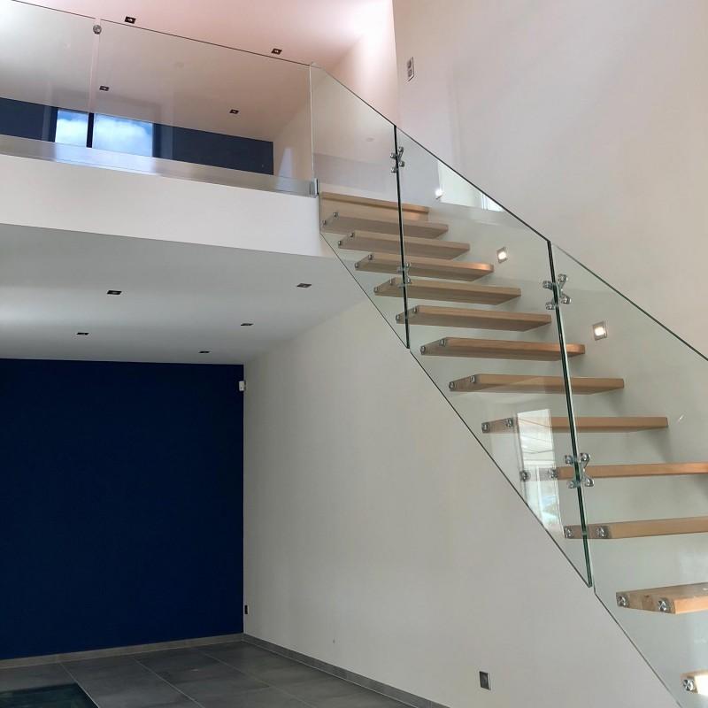 Escalier moderne à marches suspendues en bois et garde-corps en verre