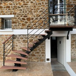 Escalier extérieur à limon central métallique et marches en bois exotique
